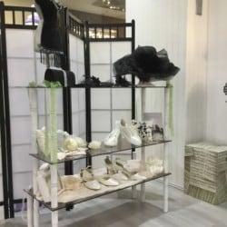 Glasregal mit Brautschuhen, Ringkissen, Fascinator und Brauthut